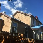 neighbors getting new asphalt shingles on roof of house