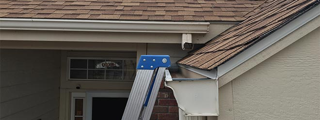 ladder leaning on gutter to perform roof and gutter maintenance