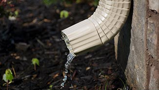 a rain gutter with rain water flowing out